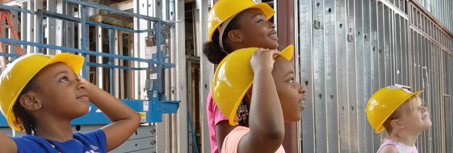 Kids in construction hats looks at the progress of the MCM Meridian building