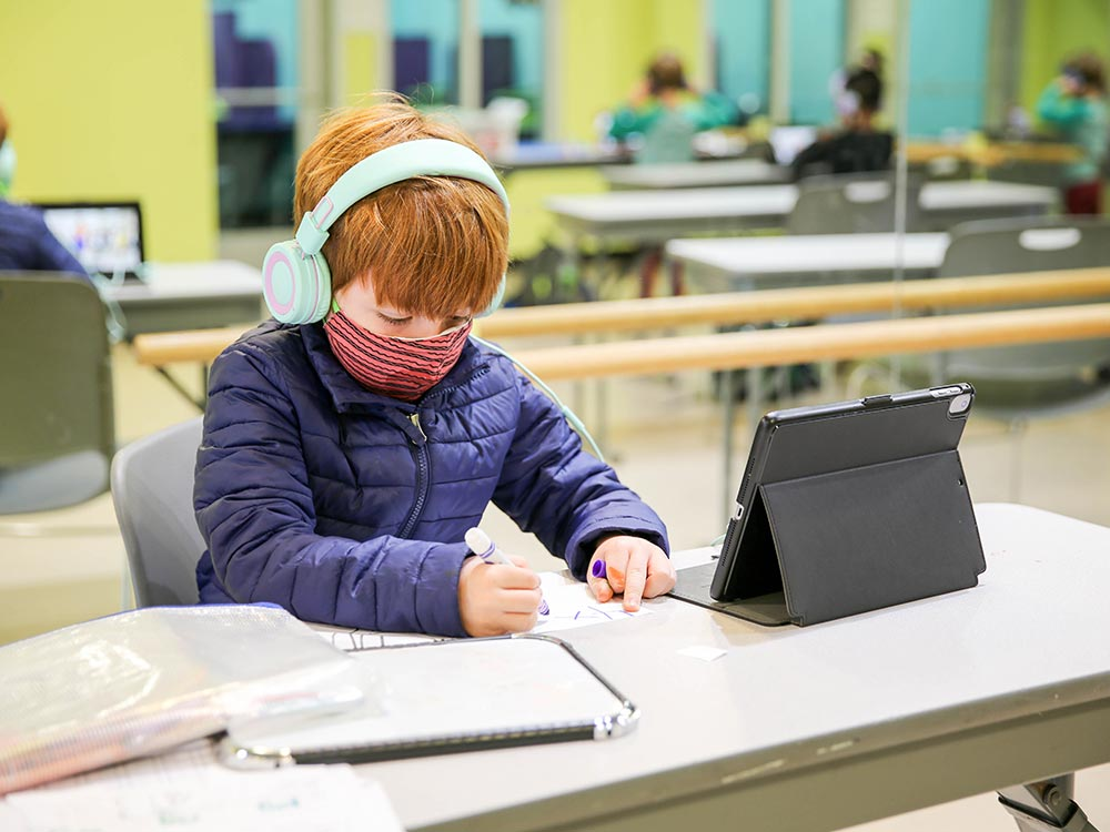 Young boy working on school with a mask and headphones on.