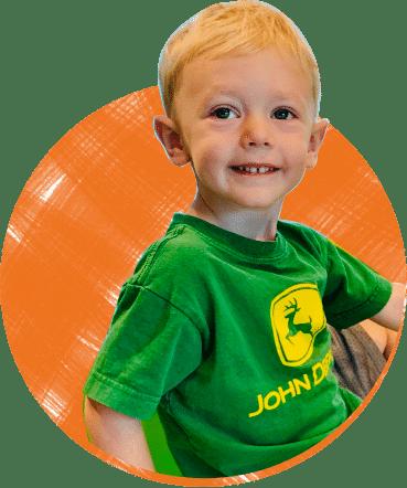 Boy in green shirt on orange background