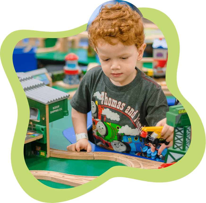 Little boy playing with a train set at the Mississippi Children's Museum