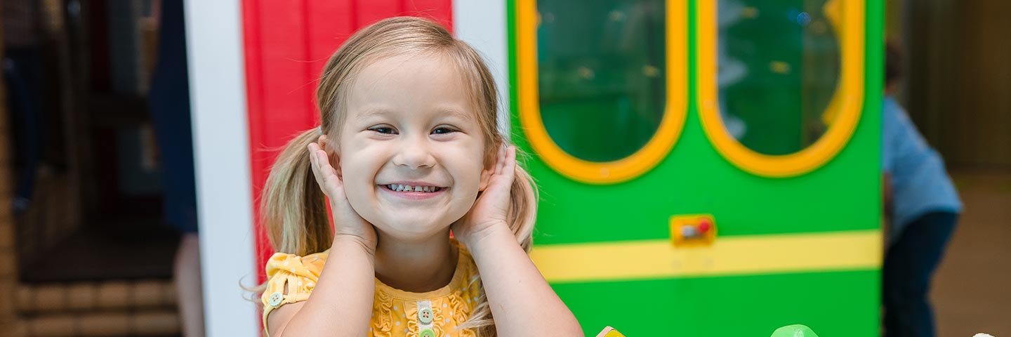 Little girl with pigtails playing at the Mississippi Children's Museum.
