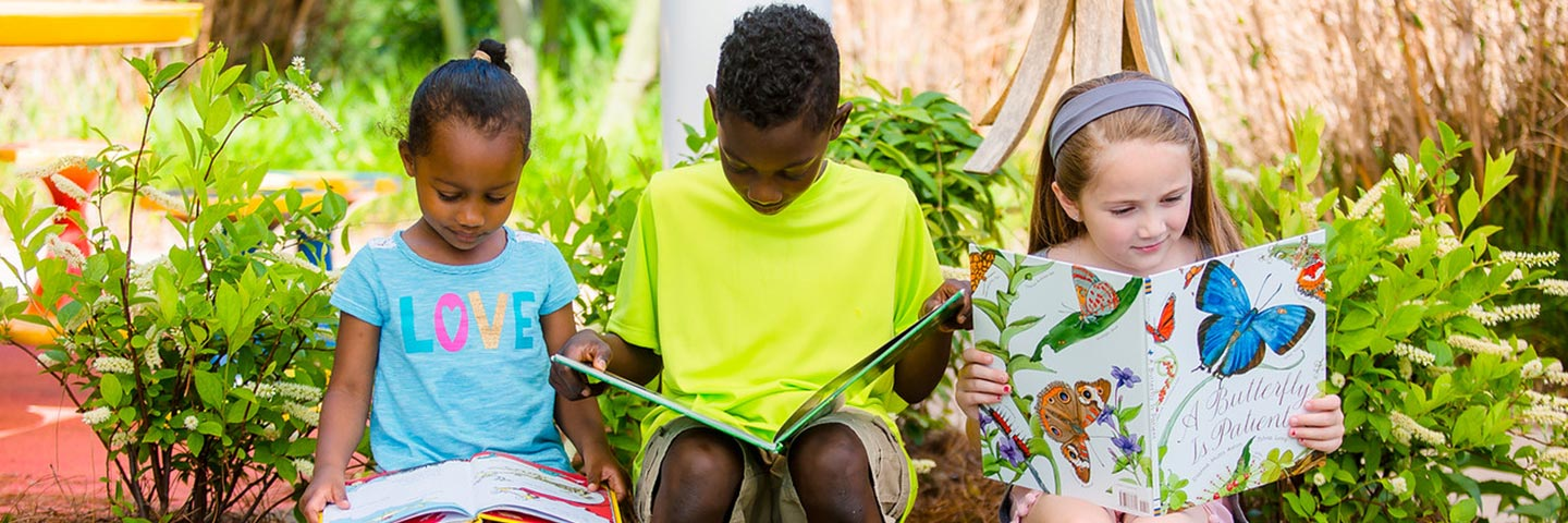 Kids sitting in a garden reading books