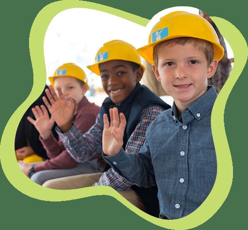 Kids wearing construction hats waving.