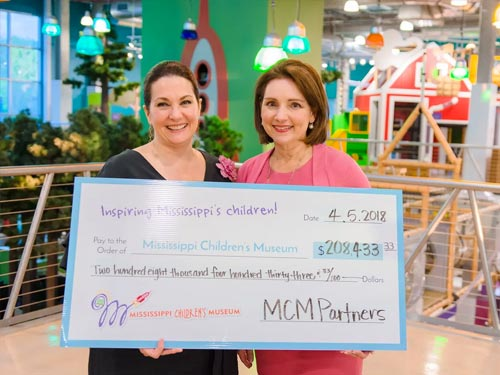 Two women holding check