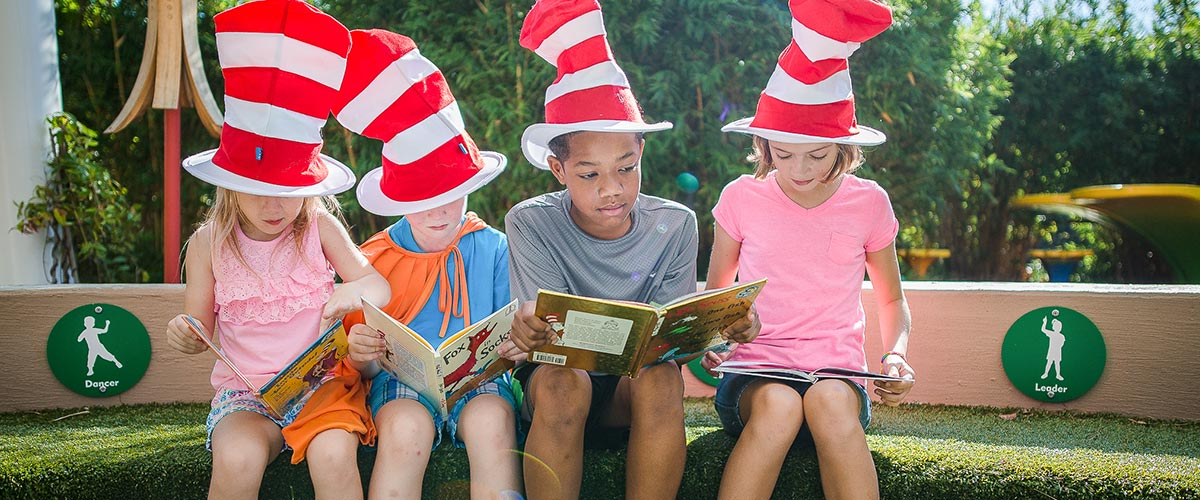 Kids wearing Dr. Seuss hats and reading books.