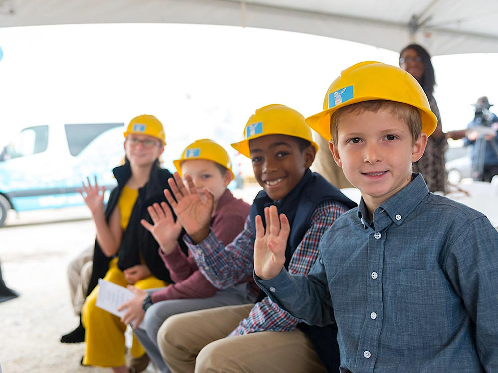 Group of kids with hard hats waving at the camera.